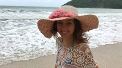 Woman with big sunhat looking out over ocean on vacation Stock Footage