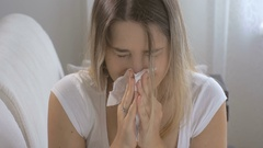 Young woman suffering from allergy sitting on sofa and sneezing in paper tissue Stock Footage