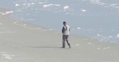 Retired Man Walking on Beach in Winter Ocean Waves Crash Close, 4K Stock Footage