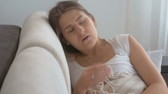 Young sick woman coughing in bed and using throat spray Stock Footage