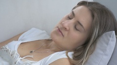 Closeup shot of young sick woman lying on pillow and coughing Stock Footage