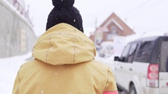 Woman in yellow parka and bobble hat walks along the road covered in snow Stock Footage
