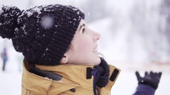 Smiling young woman in bobble hat looking up and enjoying snow fall Stock Footage