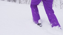 Young woman runs on the snow in purple ski pants and in snowboard boots Stock Footage