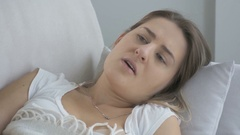 Young sick woman lying in living room and coughing Stock Footage