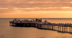 Time lapse panning view of a sunset on the beach in Brighton Stock Footage