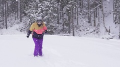 Young woman running in the snow in winter clothing Stock Footage