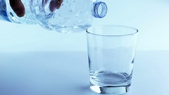 Filling a glass with water through bottle, nutrition and health-care concept Stock Footage