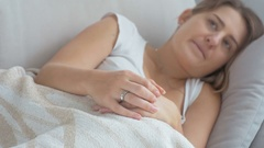 Closeup shot of upset worried woman lying in bed and rubbing fingers Stock Footage