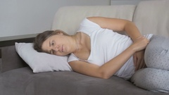 Young woman suffering from stomach ache lying on sofa at living room Stock Footage