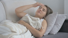 Unhappy young woman suffering from headache lying couch at living room Stock Footage