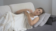Young depressed woman lying on sofa at living room Stock Footage
