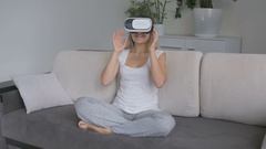 Woman in living room  wearing VR headset watching 360 degree video Stock Footage