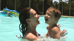 Mother and child at the swimming pool  Mom holding her kid and playing Stock Footage