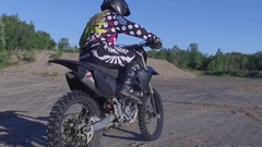 Motocross female rider kickstarts her dirt bike Stock Footage