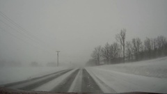 POV dashcam driving in blowing snow whiteout and near blizzard conditions Stock Footage