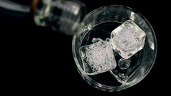 Barman pouring whiskey with ice cubes in the glass on wood table Stock Footage