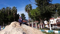 Child sits on the top of big sand pile and scatters sand Stock Footage