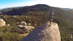 Aerial shot of young man mountain biker resting with his bike on a boulder. Stock Footage