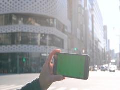 Green Screen - Japanese woman using smartphone downtown Tokyo, Japan Stock Footage