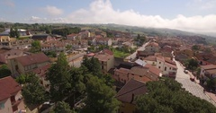 Aerial 4k drone shot above a beautiful small town with clouds and mountains Stock Footage