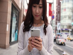 Slow motion footage of young Japanese woman walking with smartphone in luxury Stock Footage
