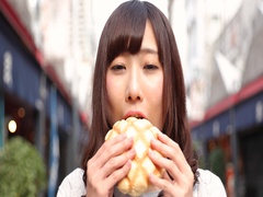 Footage of young Japanese woman eating bread in traditional shopping street Stock Footage