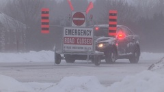 Police car and road closed sign during winter snow storm Stock Footage