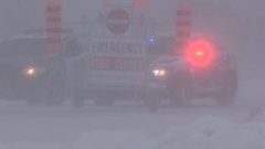 Road closed sign and police car with flashing lights in snow storm Stock Footage