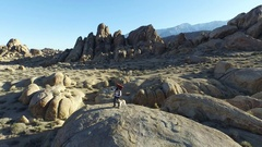 Aerial shot of a young man backpacker standing on a boulder with his dog in a de Stock Footage