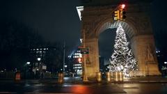 Panning medium shot of Washington Square Park arch with Christmas tree night NYC Stock Footage
