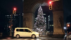 Washington Square Park North arch with Christmas tree lights car driving NYC Stock Footage