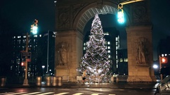Man jogging on Washington Square Park North across arch with Christmas tree NYC Stock Footage
