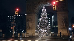 People looking at Christmas tree under Washington Square Park arch at night NYC Stock Footage