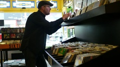 Man with black shirt browsing records in the vinyl record store Stock Footage