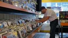 Man with white shirt browsing records in the vinyl record store Stock Footage