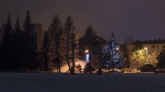 Panorama over buildings and trees covered with snow illuminated by lam Stock Footage