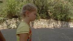 Upset girl complains dad because of the heat in the Park. Sits down next to him Stock Footage