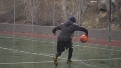 A young man basketball player practicing his ball handling outdoors in the freez Stock Footage