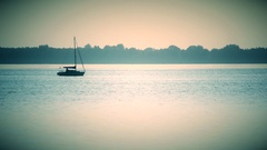 Sail boat far off on a lake or river Stock Footage