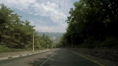 View from car traveling along scenic green road with high mountains on horizon Stock Footage