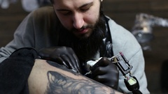 Tattoo master in black gloves, tattooing on the skin Stock Footage