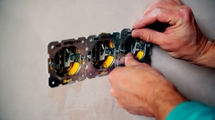 Electrician hands install electrical wall sockets Stock Footage