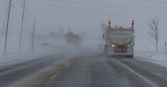 Driving in snow and blizzard behind a snow plow on the highway Stock Footage