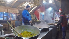 Preparing asian food in the Asian food stall at Central Christmas Market in Kiev Stock Footage