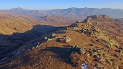 Beautiful rocky mountain crest aerial golden orange grass horizon skyline sunny Stock Footage