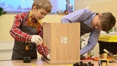 Boys tightening screws in wooden stool Stock Footage