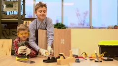 Children in the workshop construct wooden stool Stock Footage
