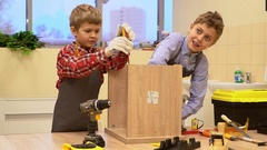 Two boys with screwdrivers and tools repairing wooden stool Stock Footage