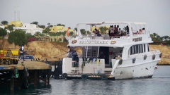 Cruise Boat with Passengers Approaches to the Pier in the Red Sea. Slow Motion Stock Footage